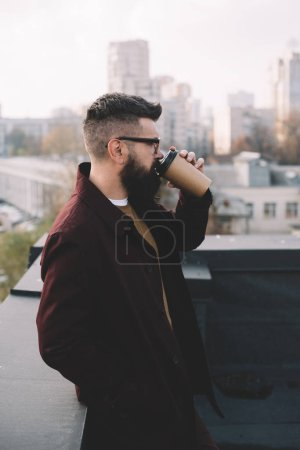 Photo for Stylish adult man in glasses holding coffee to go on rooftop - Royalty Free Image