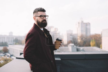 Photo for Focused stylish adult man in glasses holding coffee to go on rooftop - Royalty Free Image