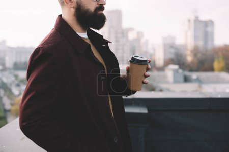 Photo for Cropped view of stylish adult man in glasses holding coffee to go on rooftop - Royalty Free Image