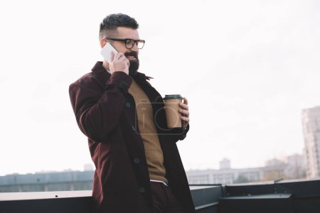 stylish adult man in glasses talking on smartphone and holding coffee to go on rooftop