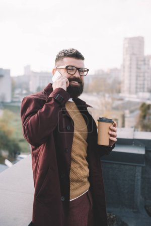 Photo for Stylish adult man in glasses talking on smartphone and holding coffee to go on rooftop - Royalty Free Image