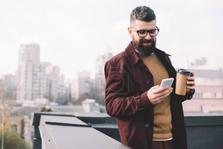 Photo for Stylish adult man in glasses holding coffee to go and using smartphone on rooftop - Royalty Free Image