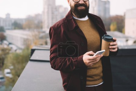 Photo for Cropped view of stylish adult man in glasses holding coffee to go and using smartphone on rooftop - Royalty Free Image