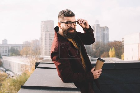 Photo for Stylish adult man in glasses looking at camera and holding coffee to go on rooftop - Royalty Free Image