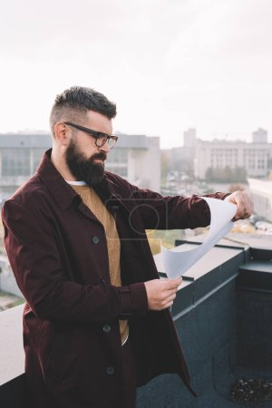 serious adult male architect in glasses holding blueprint and working on project on rooftop