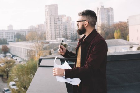 adult male architect in glasses holding blueprint and working on rooftop with beautiful view