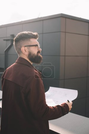 handsome adult male architect in glasses holding blueprint on rooftop