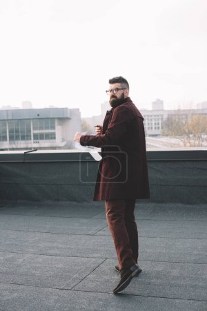 adult male architect in glasses holding blueprint and looking at camera on rooftop