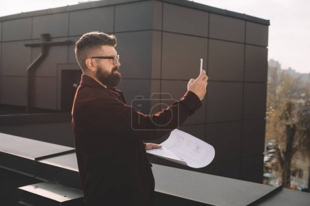 serious adult male architect in glasses taking photo and holding blueprint on rooftop