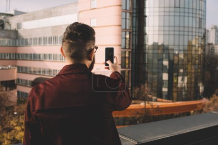 Photo for Rear view of adult man taking selfie on rooftop with beautiful view - Royalty Free Image