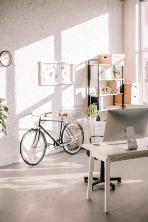 Photo pour Design de bureau moderne avec tableau à feuilles mobiles, vélo et bureau informatique - image libre de droit