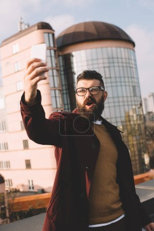 Photo for Surprised adult man taking selfie on rooftop with beautiful view - Royalty Free Image