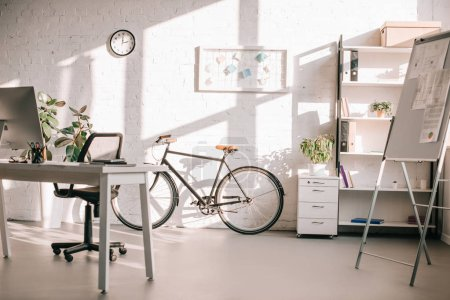 modern office design with flip chart, bicycle and computer desk