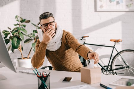sick businessman in knitted scarf sitting at office desk, coughing and reaching out for tissues