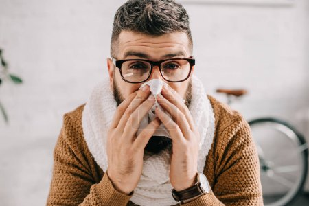 portrait of sick man in knitted scarf sitting in office, sneezing and covering mouth with tissue