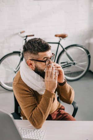 sick businessman in knitted scarf sitting in office, sneezing and covering mouth with tissue