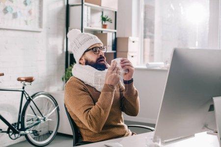 Photo pour Homme d'affaires malade en écharpe et bonnet assis au bureau et éternuements - image libre de droit