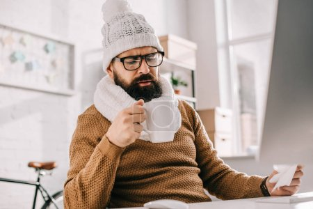 sick businessman in scarf and knitted hat holding cup of tea and tissue at workplace