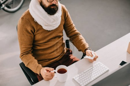 sick businessman in scarf holding cup of tea and tissue and sitting at office desk