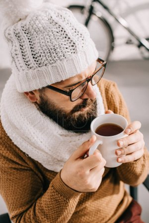close up of sick man in scarf and knitted hat holding cup of tea