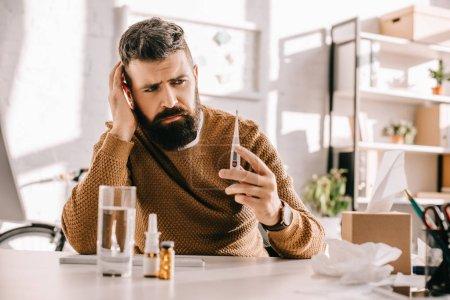 Photo pour Homme d'affaires malade tenant thermomètre médical et assis au bureau avec un verre d'eau et de médcine - image libre de droit