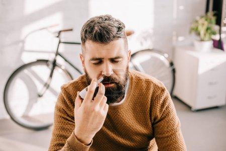 Photo pour Malade au nez qui coule par pulvérisation nasale - image libre de droit