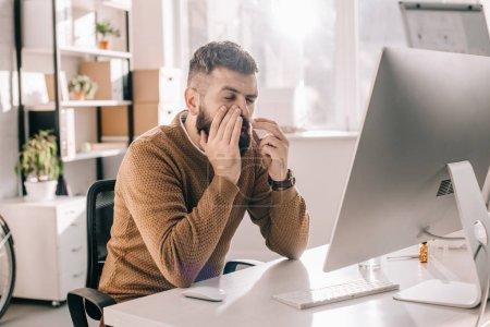 Photo pour Homme d'affaires malade assis au bureau avec liquide en utilisant pulvérisation nasale - image libre de droit