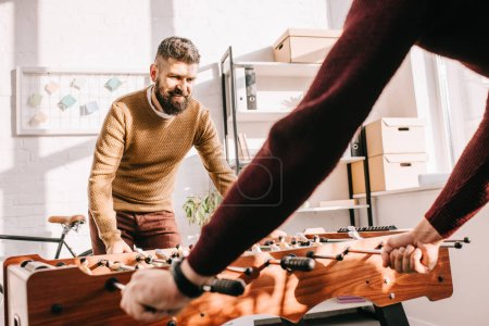 bearded adult man playing table football game with friend at home