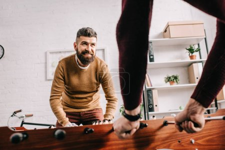smiling adult man playing table football game with friend at home