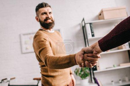 Photo pour Foyer sélectif de sourire homme adulte serrant la main avec partenaire dans le bureau - image libre de droit