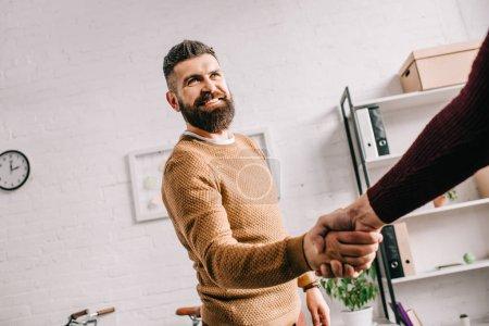 Photo pour Souriant adulte homme d'affaires, serrant la main de partenaire au bureau - image libre de droit