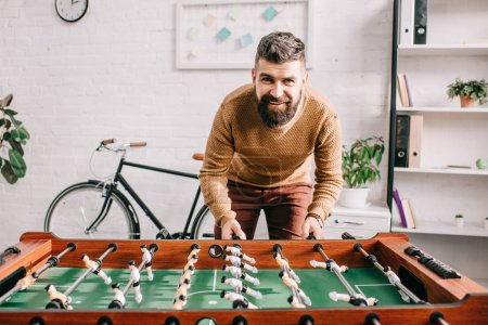smiling handsome adult man looking at camera and playing table football game at home