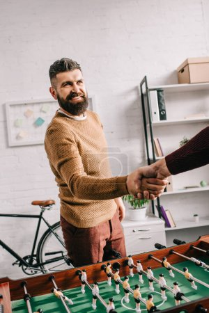 smiling adult man shaking hands with friend after playing table football game