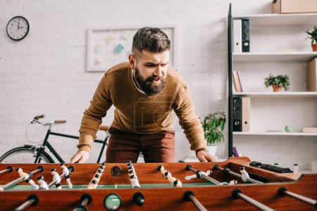 bearded adult man playing table football game at home