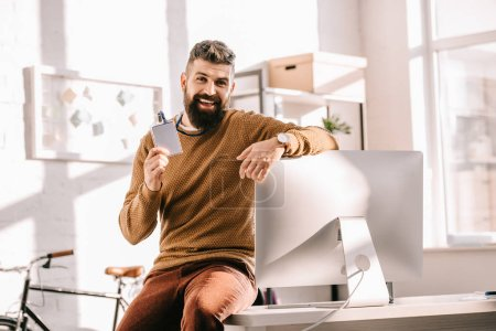 cheerful bearded adult businessman sitting on desk and pointing at blank security tag in office
