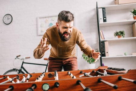 Photo for Angry adult man yelling and playing table football game at home - Royalty Free Image