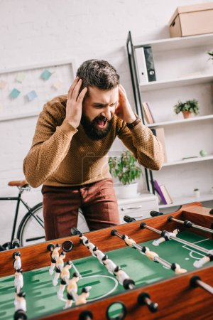 angry adult man with hands on head yelling and playing table football game at home