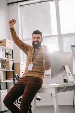 Photo for Happy bearded adult businessman wearing blank security tag and holding arms up in excitement - Royalty Free Image