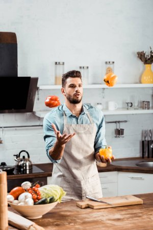 Photo for Handsome young man in apron juggling with fresh peppers in kitchen - Royalty Free Image
