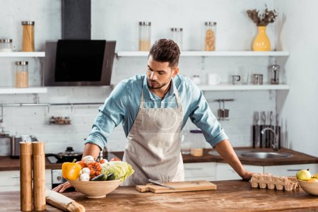 Photo for Handsome young man in apron leaning at table and looking at fresh vegetables in kitchen - Royalty Free Image