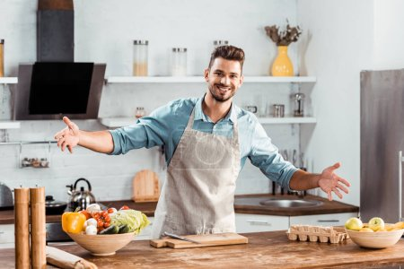 Photo for Cheerful young man in apron with open arms smiling at camera in kitchen - Royalty Free Image