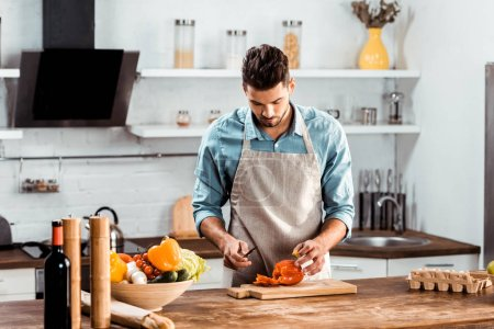Photo for Young man in apron cutting fresh pepper in kitchen - Royalty Free Image
