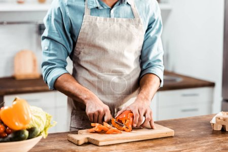 Photo for Mid section of young man in apron cutting fresh pepper in kitchen - Royalty Free Image
