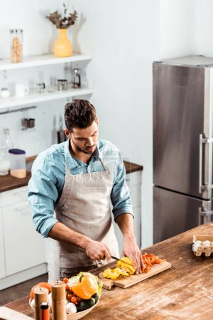Photo for High angle view of young man in apron cutting fresh peppers in kitchen - Royalty Free Image