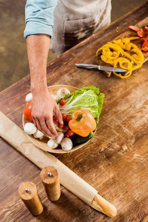 Photo for Cropped shot of man in apron cooking vegetable salad in kitchen - Royalty Free Image