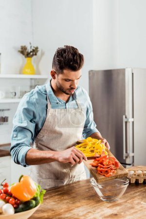 Photo for Handsome young man in apron preparing vegetable salad in kitchen - Royalty Free Image