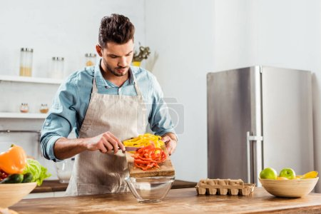 Photo for Young man in apron preparing vegetable salad in kitchen - Royalty Free Image