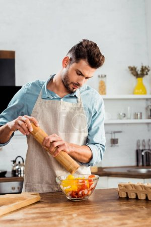 young man in apron adding pepper with mill into vegetable salad