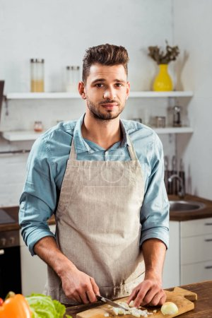 Photo for Handsome young man in apron chopping onion and looking at camera in kitchen - Royalty Free Image