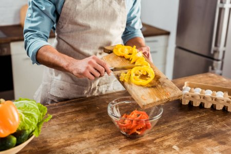 Photo for Mid section of man in apron cooking vegetable salad in kitchen - Royalty Free Image